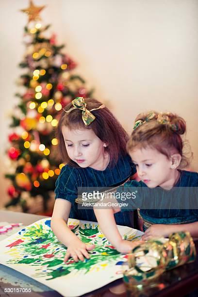 Zwei kleine Mädchen, die Malerei mit Handprints Erstes Weihnachtsfest