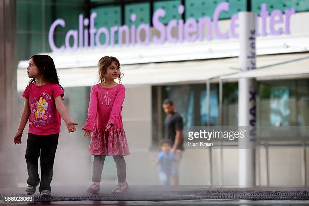 Two little girls play in the mist emitting fountain at California Science Center on Wednesday morning where a board meeting took place to discuss a...