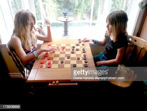 Two little girls playing checkers