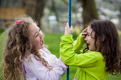 Two Little Girls Playing on Rope Swing and Laughing