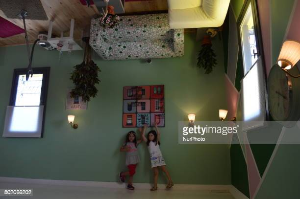 Two little girls pose for a picture inside an upsidedown house at Cheerful Village in Ankara Turkey on June 27 2017 The 14th upsidedown house in the...
