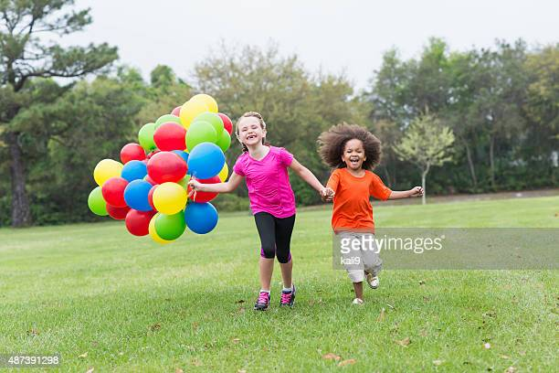 Two little girls running with bunch of balloons at park