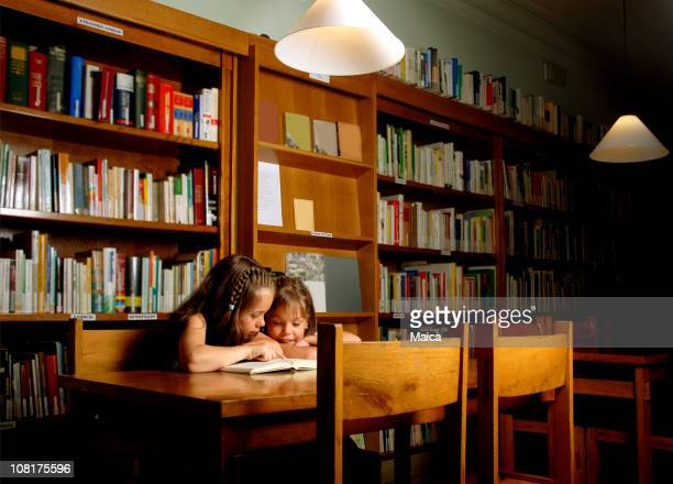 Two Little Girls Sitting in Library and Reading