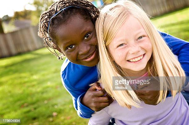 Two Little Girls Smiling and Riding Piggyback Outside