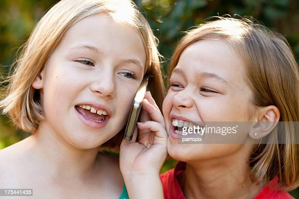 Two little girls smiling talking on mobile cell phone outdoors