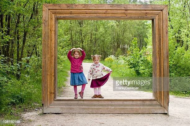 Two Little Girls Standing in Wooden Picture Frame at Forest