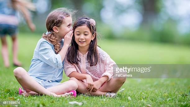 Two Little Girls Whispering