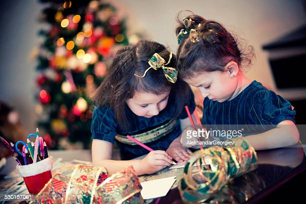 Two Little Girls Writing Their Wishes on Letter to Santa