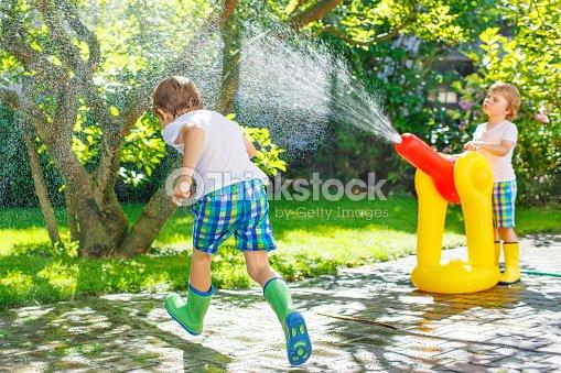 zwei kleine kinder spielen mit schlauch und wasser garten stock foto thinkstock. Black Bedroom Furniture Sets. Home Design Ideas