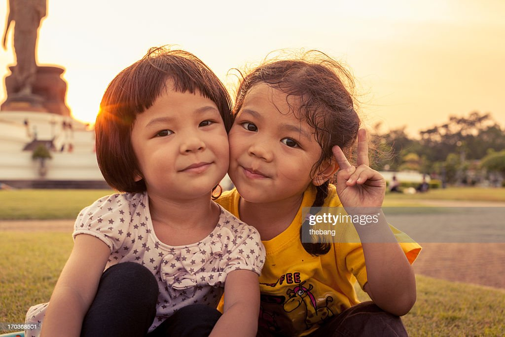 Two little kids sitting on grass