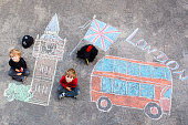Two funny kid boys in british queen's guard soldier and policeman uniform having fun with London picture drawing with colorful chalks. With Big Ben, Union Jack and red bus.