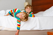 Two adorable little sibling kid boys having fun in bed after sleeping at home, indoor. Brothers smiling at the camera. Family, vacation, childhood concept. Selective focus on one child