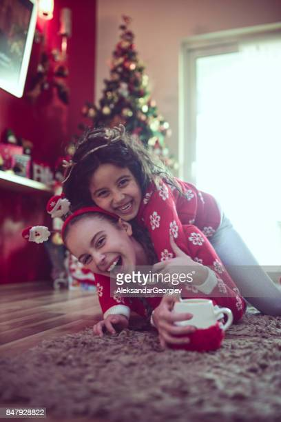 Two Little Sisters Hugging Under Christmas Tree and Drinking Hot Beverage