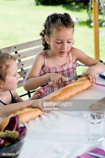 two little sisters sharing bread at table in garden