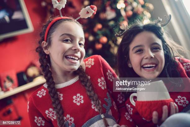 Two Little Sisters Sitting Under Christmas Tree and Drinking Hot Beverage