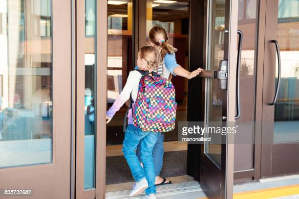 Two littles girls back to school enter in the school