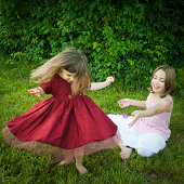 Two littles girls playing on the summer grass.