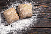 Two small loaves of ciabatta on a old wooden table, top view with space for text