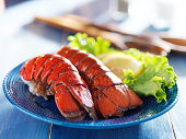 two lobster tails on blue plate with garnish for dinner shot with selective focus