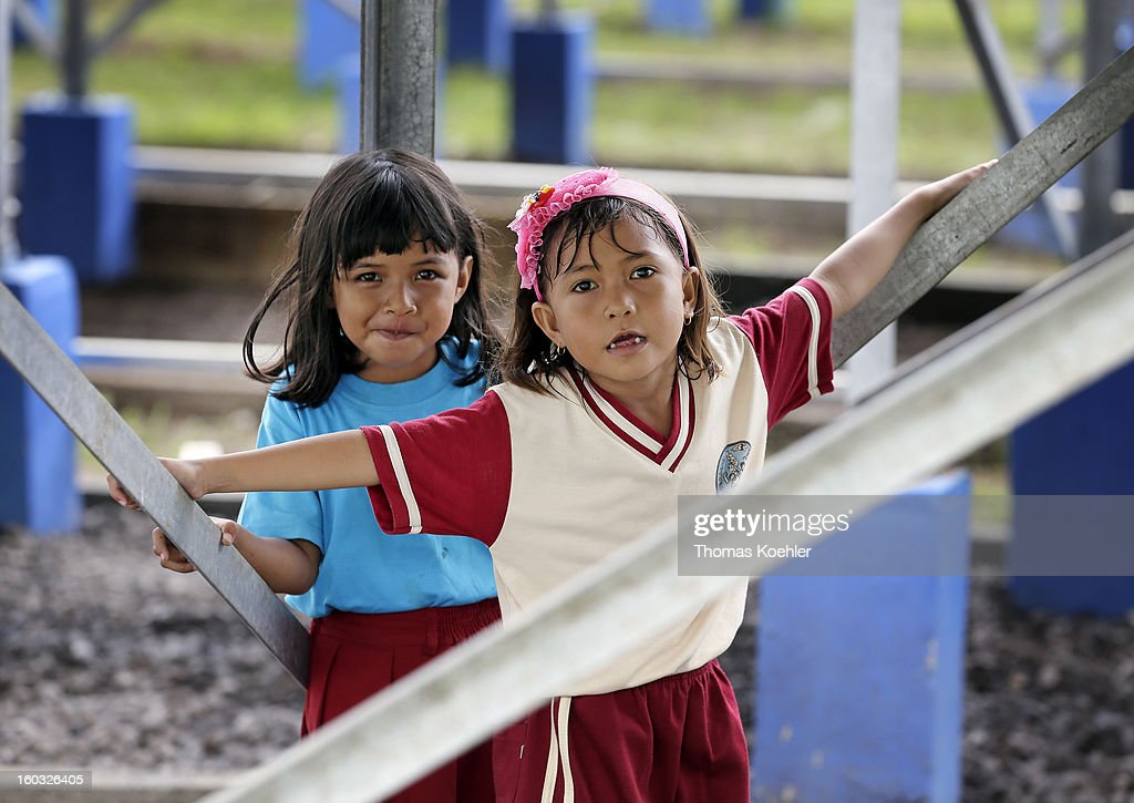 Two local Indonesian girls playing under the solar panals at the solar energy plant situated on the island of Bunaken near Manado, Indonesia, pictured on January 11, 2013.