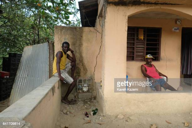 Two local Palenquero men sit idly outside a building with cracked walls on January 28 2017 in San Basilio de Palenque Colombia Centuries ago escaped...
