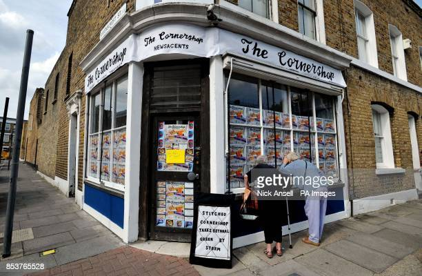 Two local residents try to peek inside The Cornershop in Wellington Row Bethnal Green east London an art installation by textile artist Lucy Sparrow...