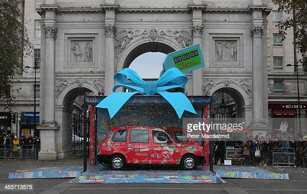 Two London taxis covered in iconic Cath Kidston prints burst out of a giant present at Marble Arch to celebrate the opening of the largest Cath...