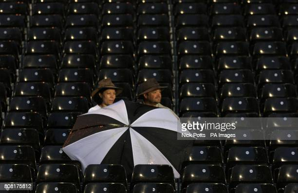 Two lone fans sit in the stands with an umbrella to shiedl them from the rain