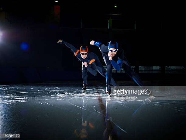 Two long track speed skaters racing on track