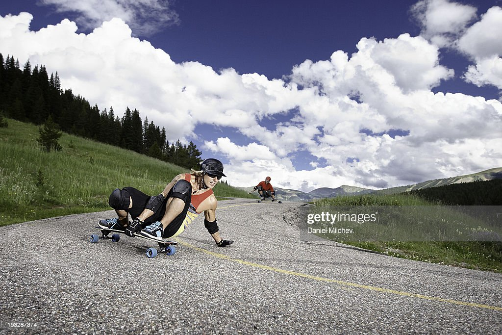 Two longboarders taking a sharp turn. : Stock Photo