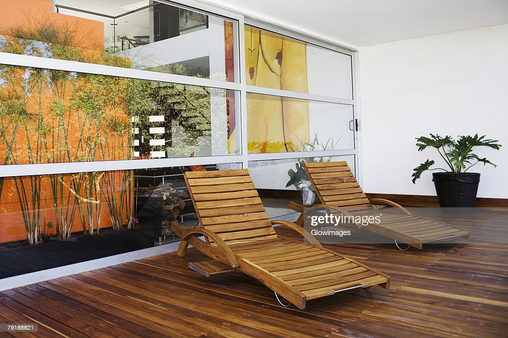 Two lounge chairs in a patio of a house : Foto de stock