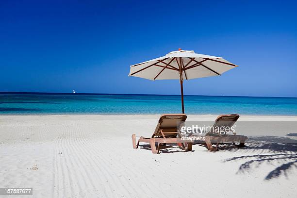 Two lounge chairs lying on a clear beach under a parasol