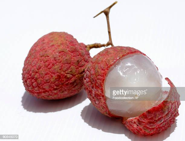 Two lychees, one partly peeled, close up