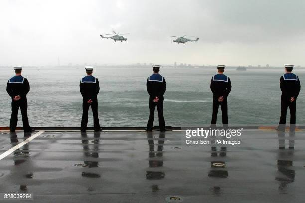 Two Lynx helicopters perform a flypast as the former flagship of the Royal Navy HMS Invincible sails into Portsmouth for the last time before it is...