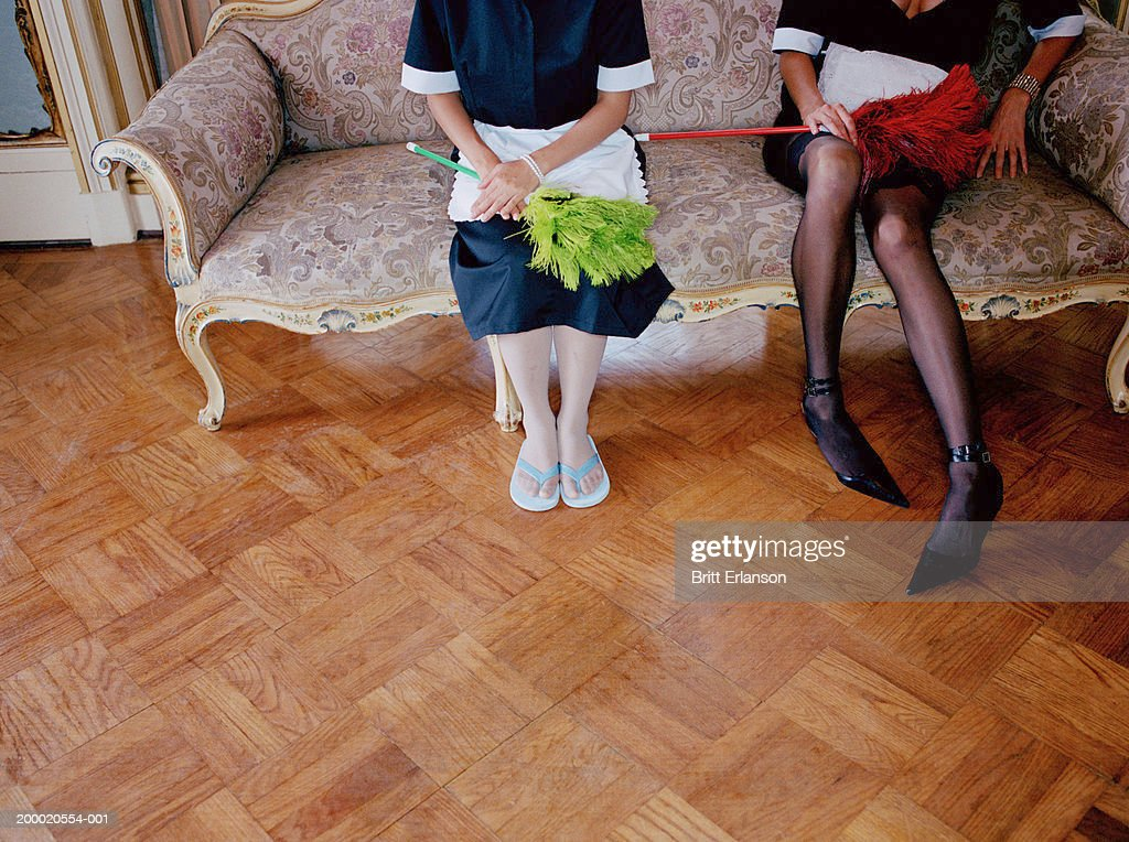 Two maids on sofa, low section : Stock Photo