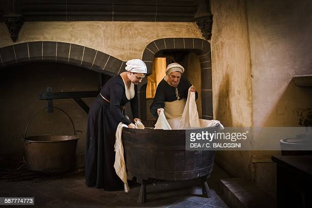 Two maids washing sheets in a tub in the kitchen of a house 15th century Historical reenactment