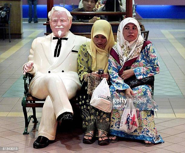 Two Malaysian women sit next to Colonel Sanders the famous icon of Kentucky Fried Chicken on a bench at a KFC outlet in Kuala Lumpur 18 July 2001...