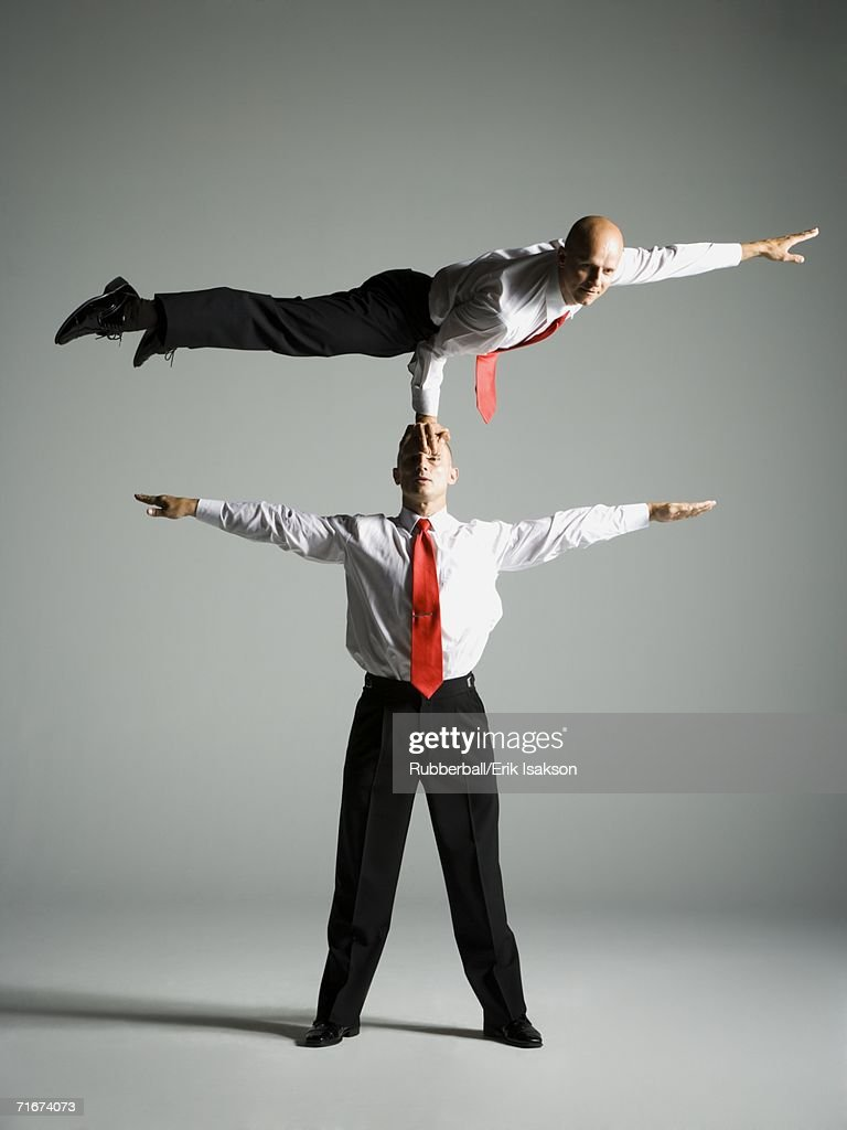 Two male acrobats in business suits
