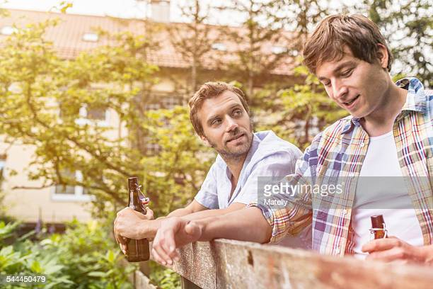 Two male adult friends chatting and drinking beer at garden fence