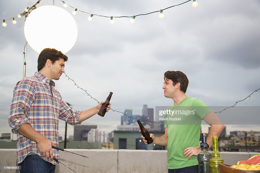 Two male adult friends chatting at rooftop barbecue