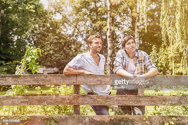 Two male adult friends leaning against garden fence