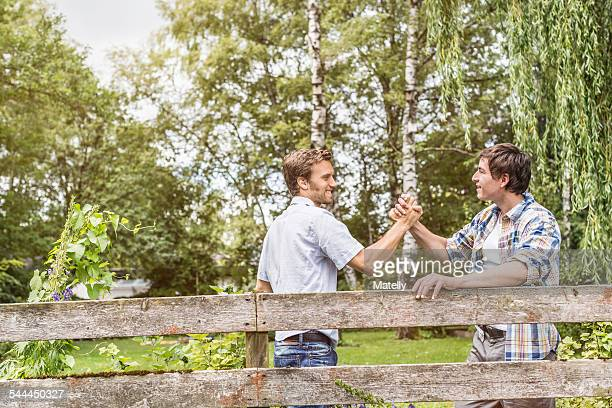 Two male adult friends shaking hands at garden fence