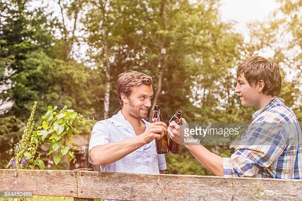 Two male adult friends toasting with beer bottles at garden fence