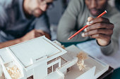 Closeup of architect's hand holding pencil pointing at architectural house model. Two male architects working on new construction project