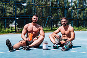 Two male athletes resting after training