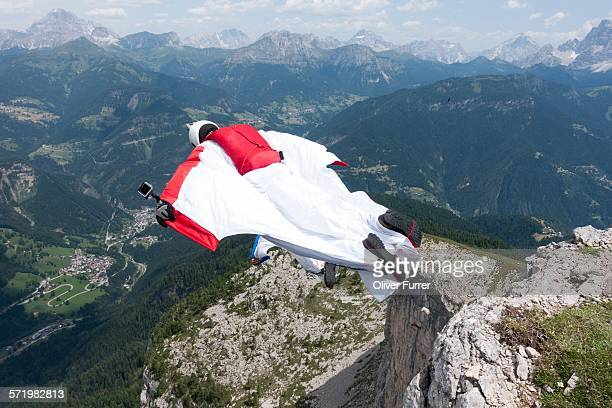 Two male BASE jumpers exiting from mountain top, Dolomites, Italy