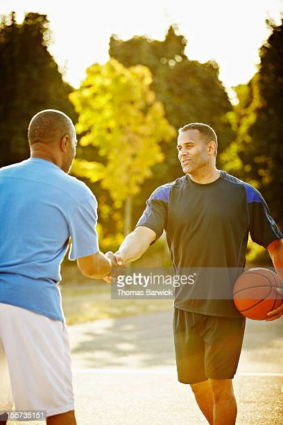 Two male basketball players shaking hands on court