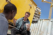 Two Male Builders Sit in a Building Site Having a Tea Break and a Chat