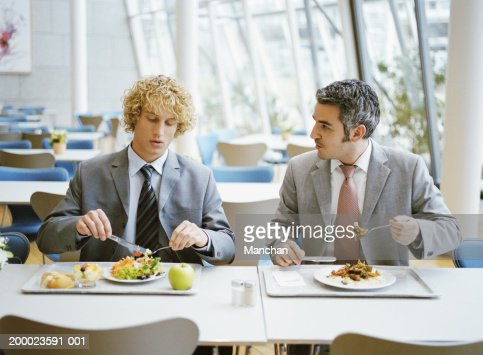 Two male business colleagues in canteen having lunch
