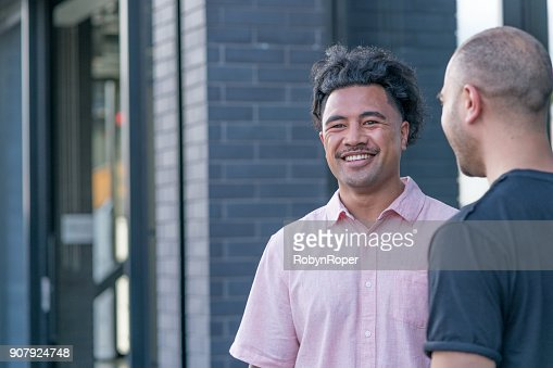 Two male business colleagues share a joke outside the office : Stock Photo